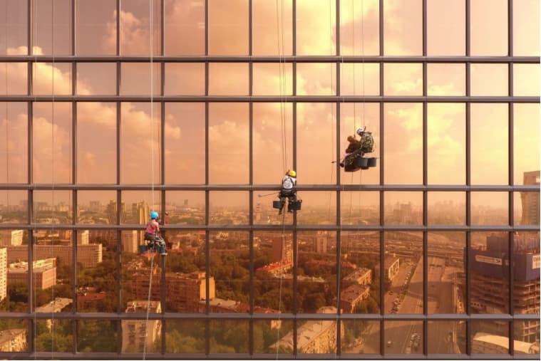 고층 빌딩 창문을 청소하는 사람들
