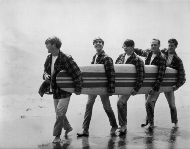 Beach Boys On The Beach With A Surfboard